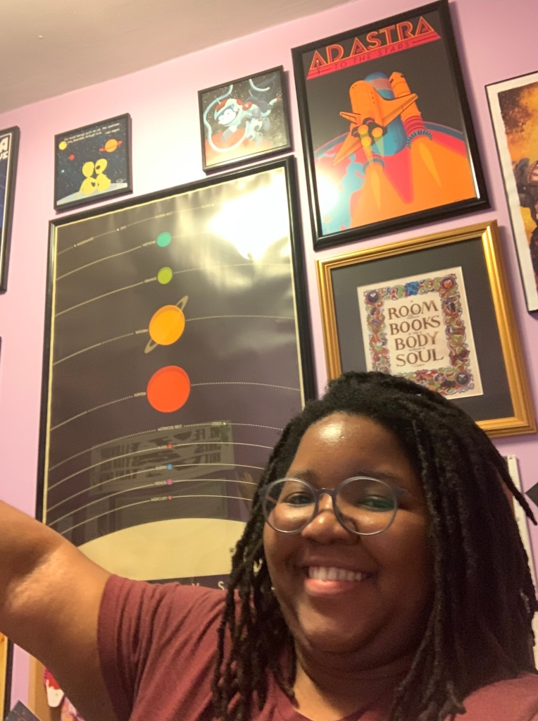Photo of Brittany standing in front of a wall of posters related to space. Caption reads 'Space Wall!'